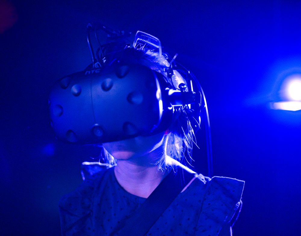 A young girl wears an HTC Vive VR Headset in a calm environment.